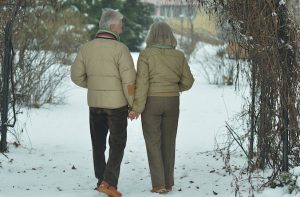 an elderly couple walking in the snow
