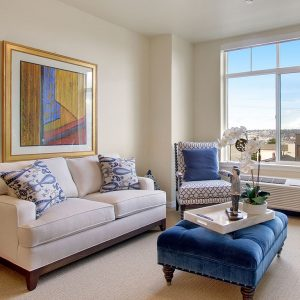 Room with white couch and blue chair with picture on wall