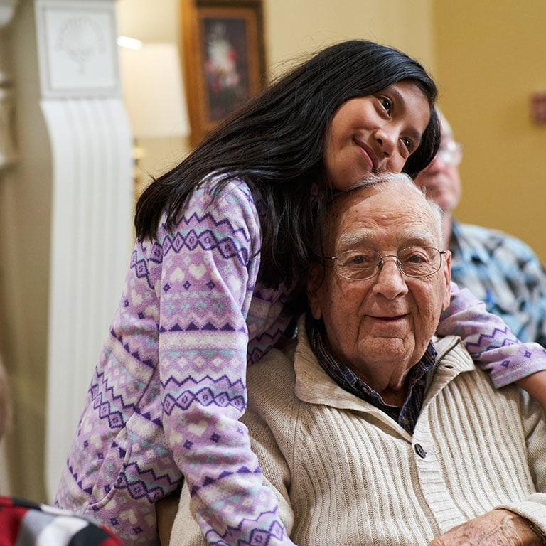 Grandchild hugging grandfather