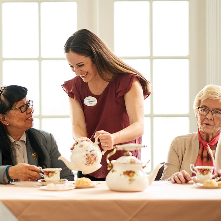 smiling staff pouring tea for residents
