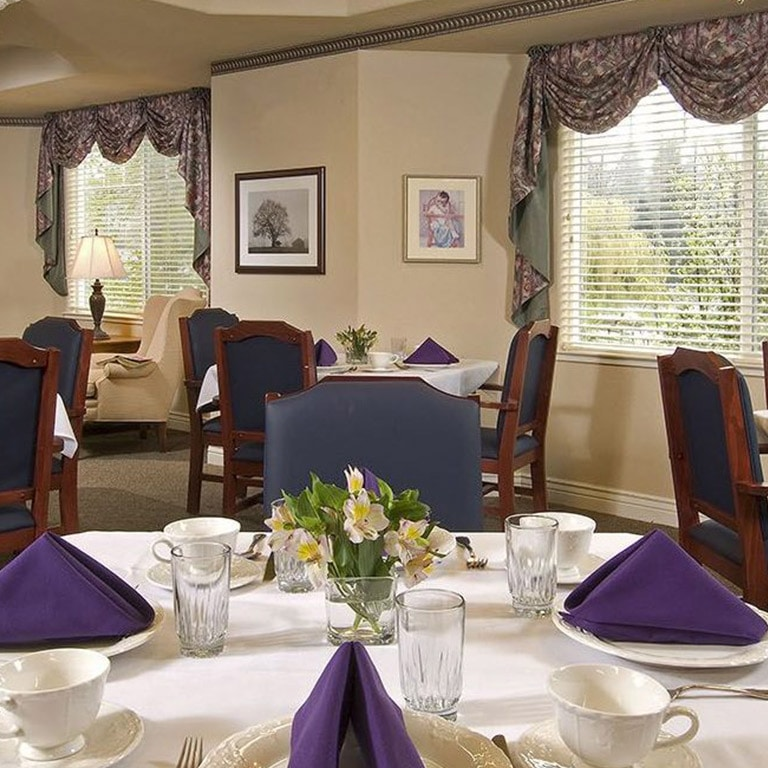 Dining room with plates on table with blue napkins on plates