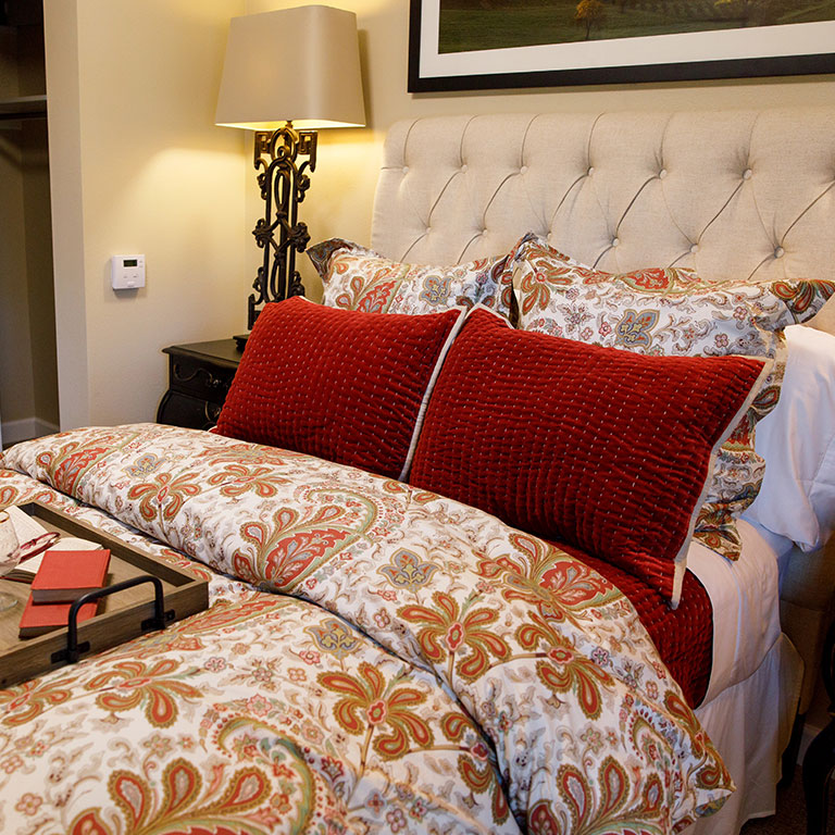 Bed with Red Pillows and Lamp