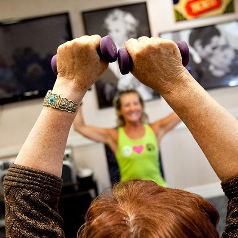 Lady with green shirt lifting weights