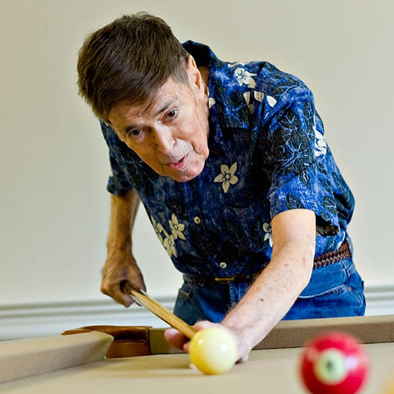 Man blue shirt playing pool