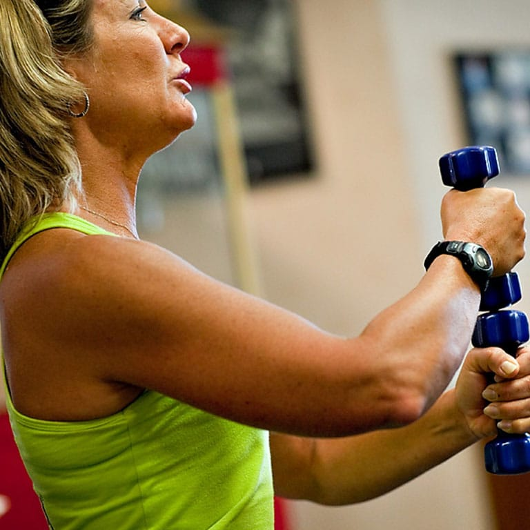 a woman holding weights working out