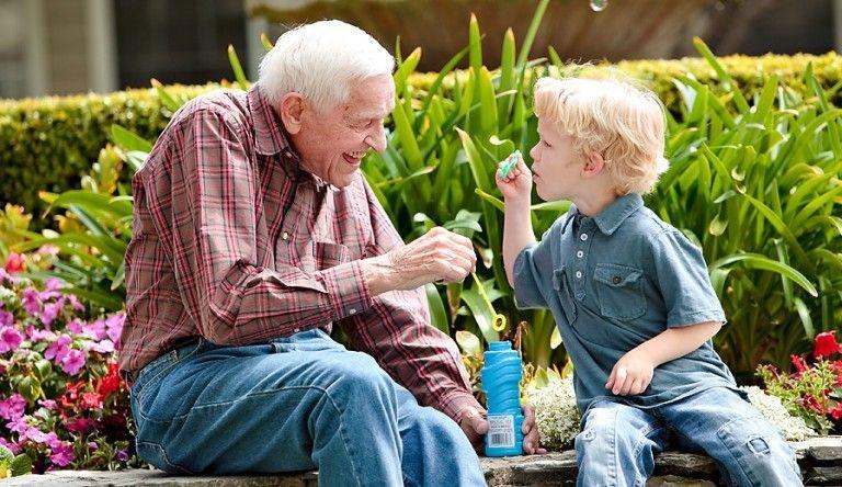 Elderly man laughs as young boy blows soap bubbles
