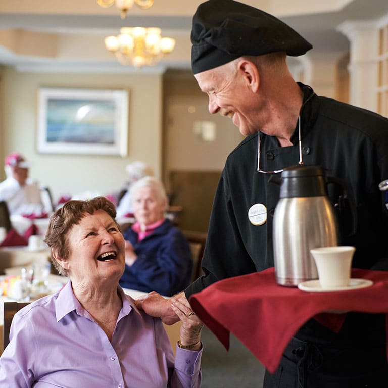 a server giving coffee to a resident