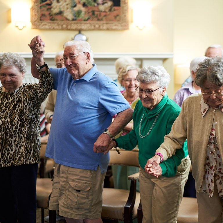 a group of seniors holding hands and having a good time