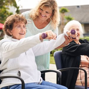 two women in chairs exercising with weights with a caretaker