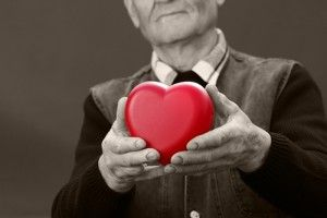 Black and white image of a senior man holding a fake pink heart.