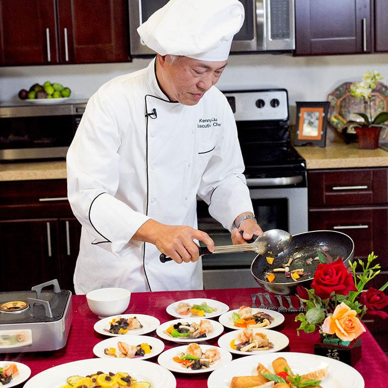 a chef plating a meal for aegis residents