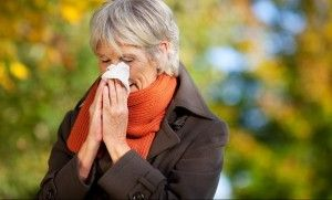 Woman in coat and scarf blows her nose