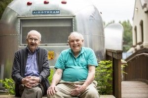 Two Aegis Living residents sit in front of an Airstream trailer in a memory courtyard