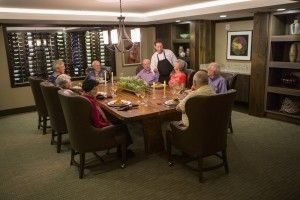 Eight Aegis Living residents at private dining room table looking toward server