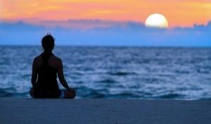 Silhouette of person meditating at sunset on a beach.