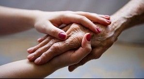 Closeup of younger woman's hands clasping elderly person's hand