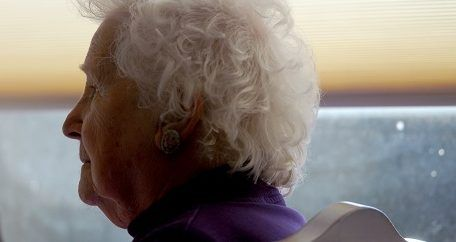 an elderly woman staring into the distance.