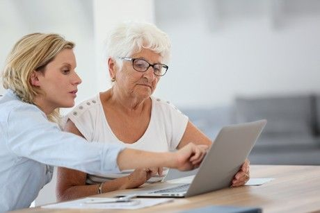Elderly woman doing her taxes with from her daughter