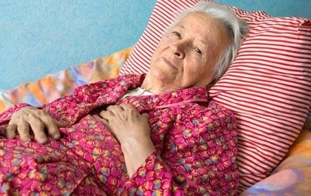 an elderly woman laying on a bed.