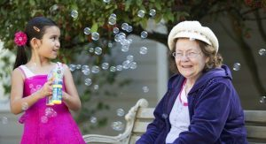 A child blowing bubbles entertains an Aegis Living resident