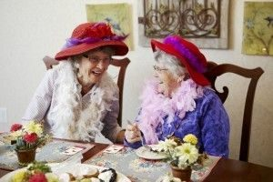 Wearing feathered boas and fancy hats brings laughter to two friends at Aegis of Living tea time