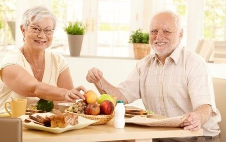 a senior couple having breakfast by a sunny window.