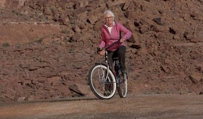 a senior woman biking on a trail.