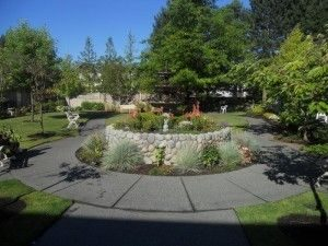 Aegis Living of Lynnwood courtyard with fountain, flowering beds and benches