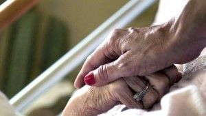 two elderly hands embracing.