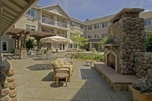 Aegis of Shoreline patio with stone fireplace, seating and fountain