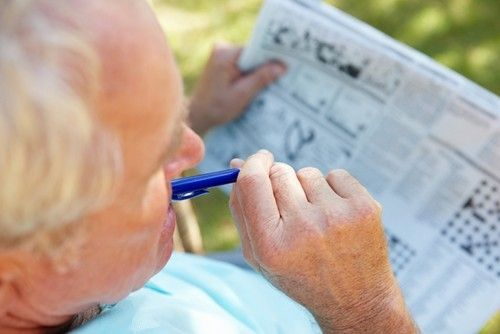 a senior man doing a crossword puzzle