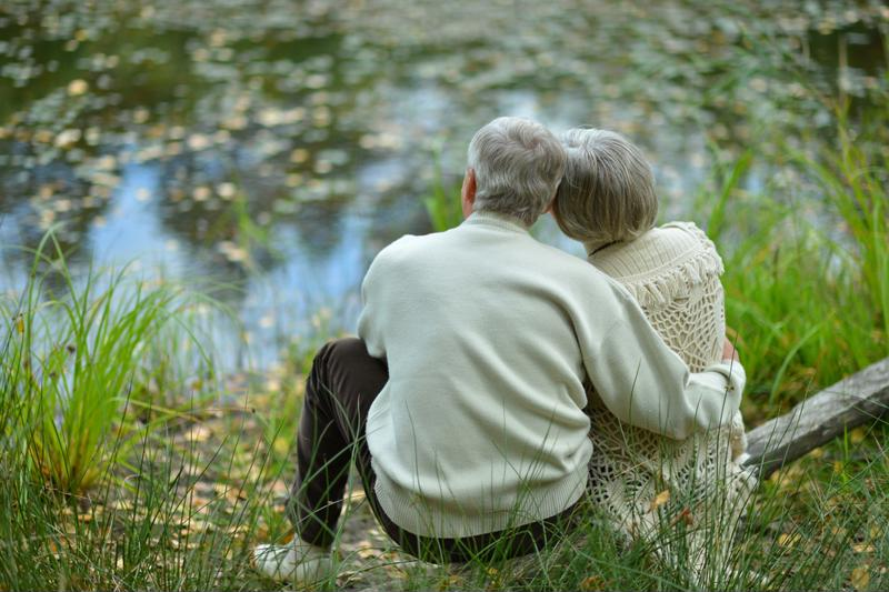 elderly couple sitting on a log looking over a lake enjoying the view