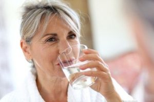 senior woman drinking water from clear glass