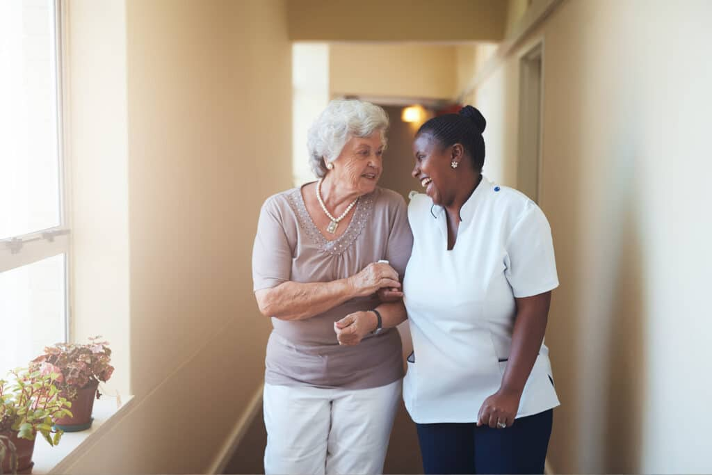 Where to Begin staff walking with resident down hallway