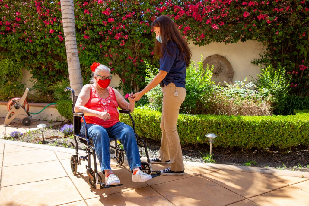 Where to Begin staff giving resident a flower in courtyard